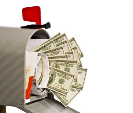Cash money spills out of a stuffed mailbox
