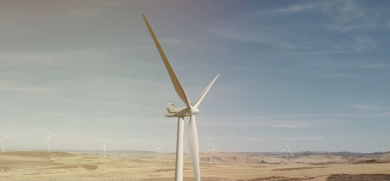 One wind turbine in the foreground with many more in the background